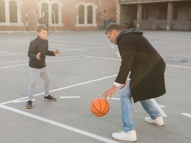 Padre e hijo jugando baloncesto Foto gratis