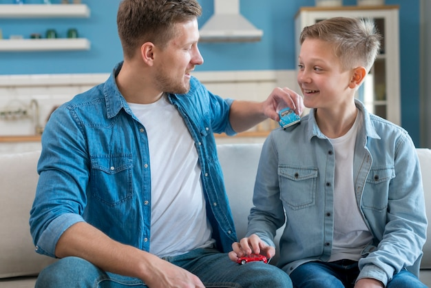 Padre e hijo jugando con carros de juguete Foto gratis