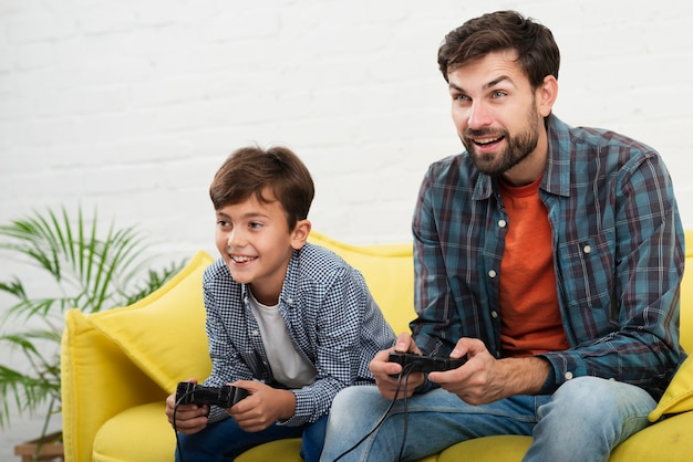 Padre e hijo jugando en la consola Foto gratis