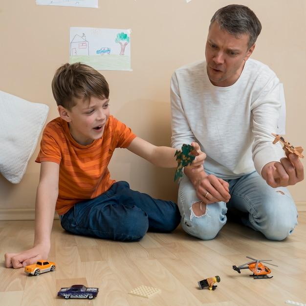 Padre e hijo jugando con juguetes en el piso Foto gratis