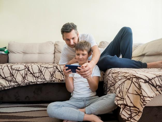 Padre e hijo jugando videojuegos en el teléfono móvil Foto gratis