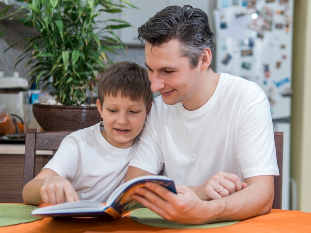 Padre e hijo leyendo un libro plano medio Foto gratis