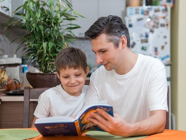 Padre e hijo leyendo un libro vista frontal Foto gratis