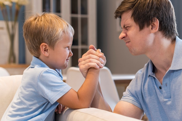 Padre e hijo, lucha libre de brazo, en casa Foto gratis