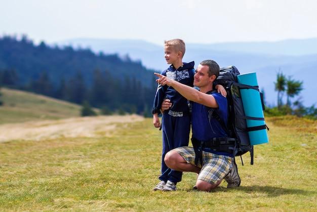 Padre e hijo con mochilas senderismo juntos en verano escénico montañas verdes. papá y niño de pie disfrutando de vistas al paisaje de montaña. estilo de vida activo, relaciones familiares, actividad de fin de semana. Foto Premium
