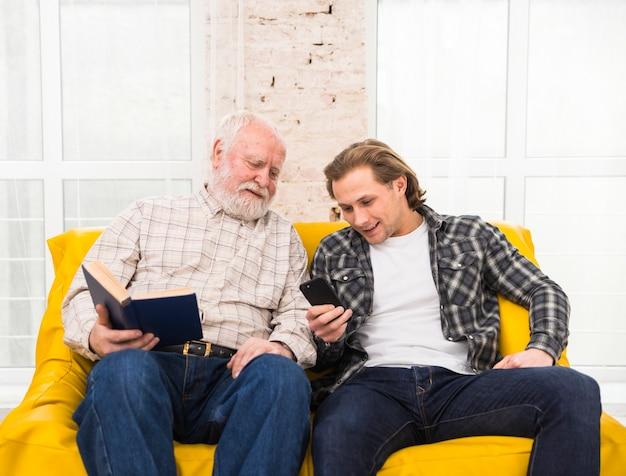 Padre e hijo navegando información en celular Foto gratis