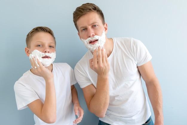 Padre e hijo parecidos con gel de afeitar Foto gratis
