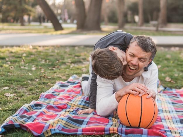 Padre e hijo con una pelota de baloncesto en el parque Foto gratis