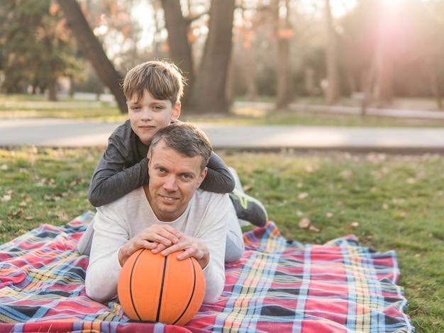 Padre e hijo con una pelota de baloncesto Foto gratis