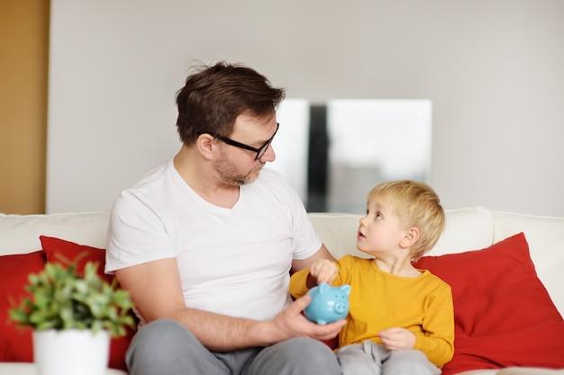 Padre e hijo poniendo monedas en la alcancía Foto Premium