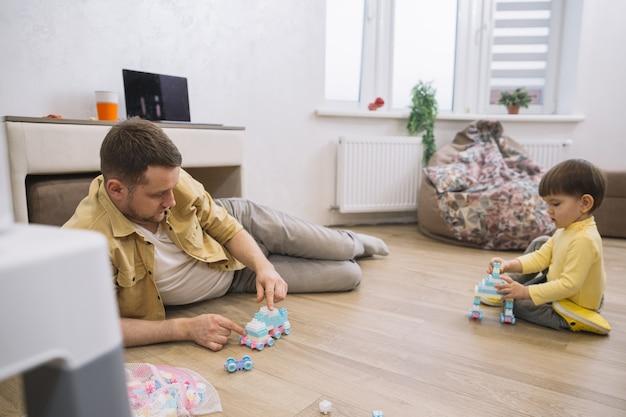 Padre e hijo en la sala de estar vista larga Foto gratis