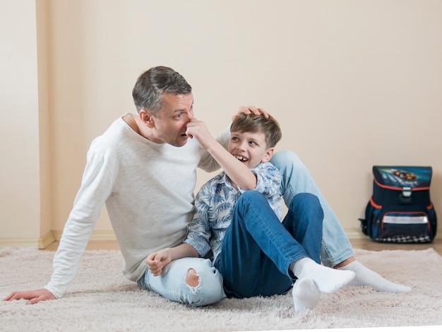 Padre e hijo sentados y jugando Foto gratis