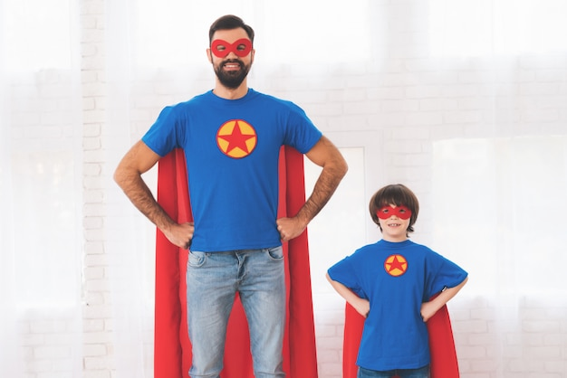 Padre e hijo en los trajes rojos y azules de los superhéroes. Foto Premium