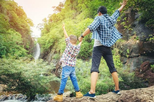 Padre e hijo viajan juntos y con los brazos abiertos celebran sus vacaciones con un gran bosque Foto Premium