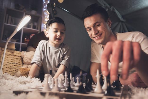 El padre enseña al pequeño hijo a jugar ajedrez en la noche en casa. Foto Premium