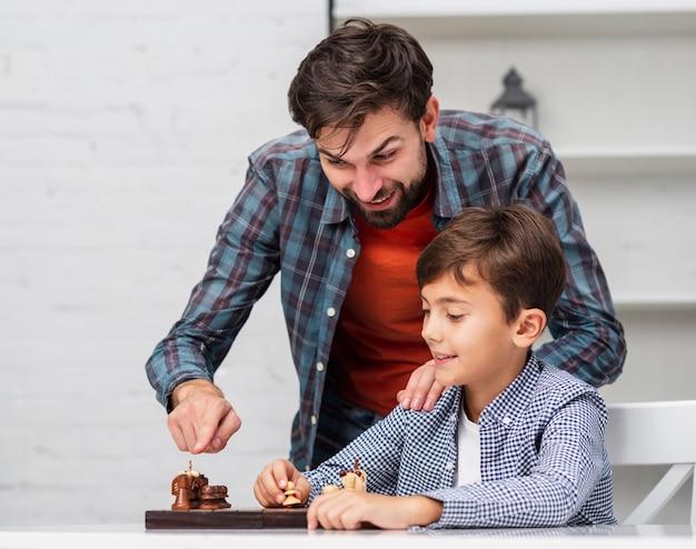 Padre enseñando a hijo a jugar al ajedrez Foto gratis