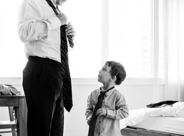 Padre enseñando a su hijo a atar un lazo Foto gratis