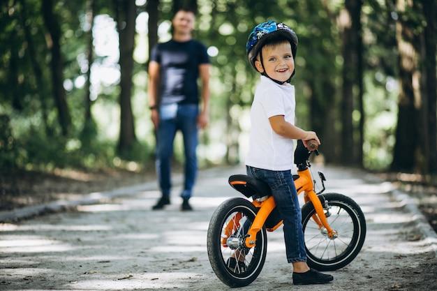 Padre enseñando a su pequeño hijo a andar en bicicleta Foto gratis