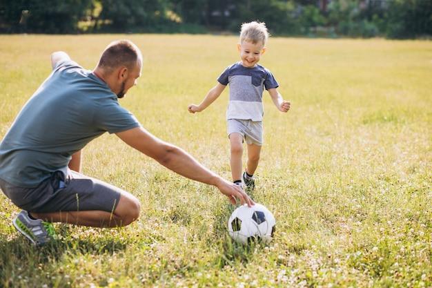 Padre con hijo jugando al fútbol en el campo Foto gratis