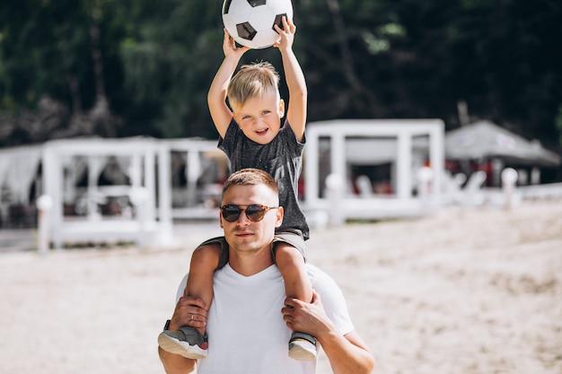 Padre con hijo jugando al fútbol en la playa. Foto gratis