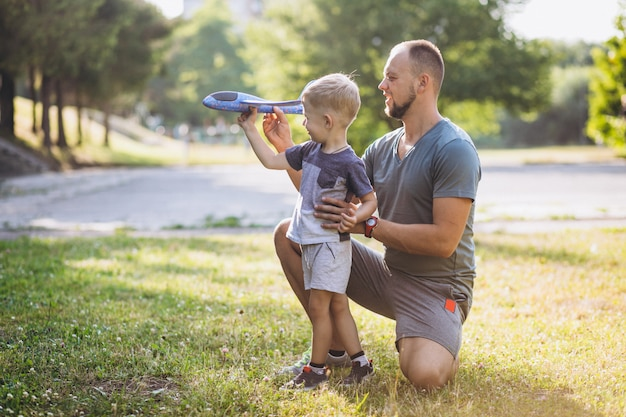 Padre con hijo jugando con avión de juguete en el parque Foto gratis