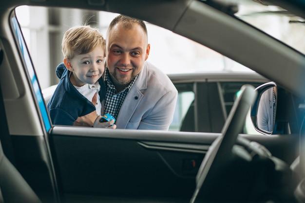 Padre con hijo mirando un coche en una sala de exposición de coches Foto gratis