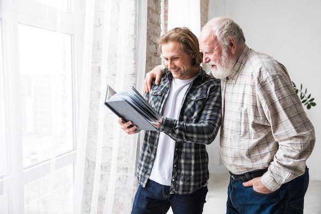 Padre con hijo viendo el álbum de fotos. Foto gratis
