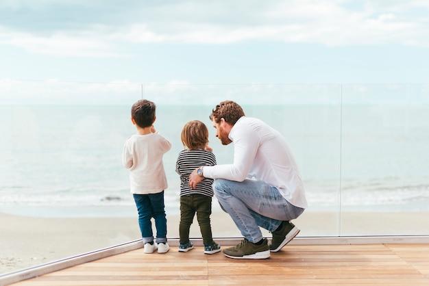 Padre con hijos mirando al mar Foto gratis