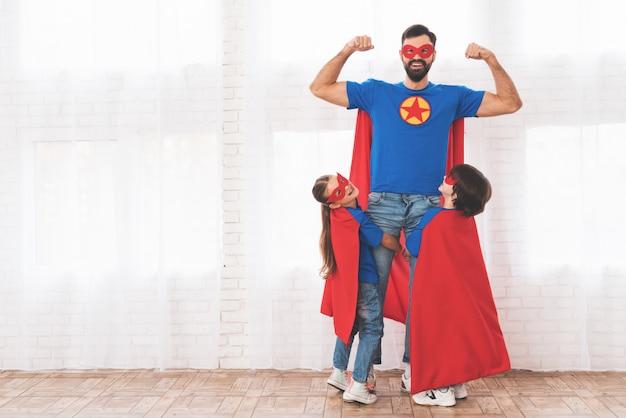 Padre con hijos en trajes rojos y azules de superhéroes. Foto Premium