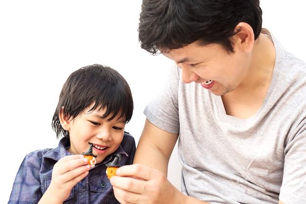 El padre está jugando la arcilla de halloween con su hijo sobre fondo blanco Foto gratis