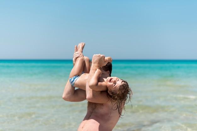 Padre jugando con el hijo a la orilla del mar Foto gratis