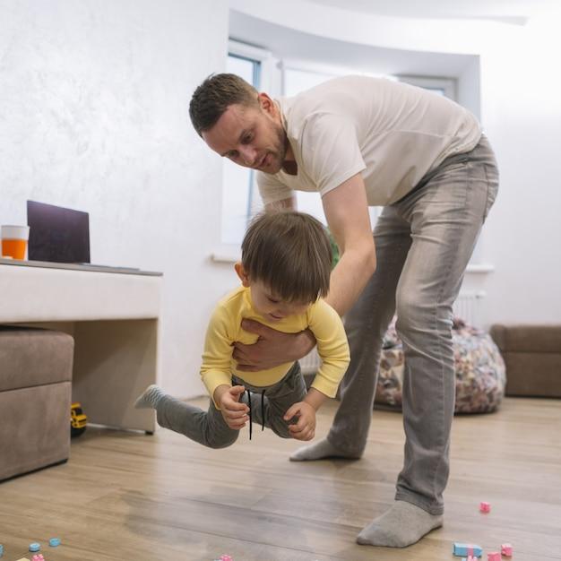 Padre jugando y sosteniendo a su hijo Foto gratis