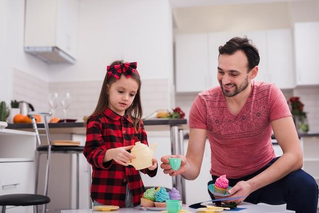 Padre jugando a las tazas con su hija Foto gratis