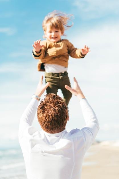 Padre lanzando riendo hijo arriba en el cielo Foto gratis