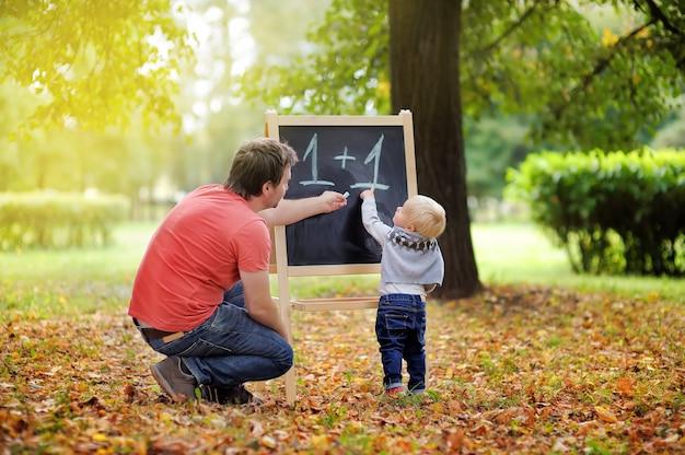 Padre de mediana edad y su hijo pequeño en la pizarra practicando matemáticas Foto Premium