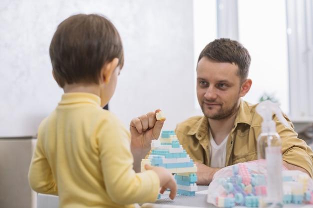 Padre mostrando un trozo de lego a su hijo Foto gratis