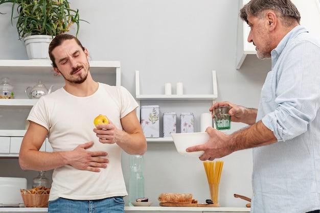 Padre ofreciendo a hijo un vaso de agua y un tazón Foto gratis
