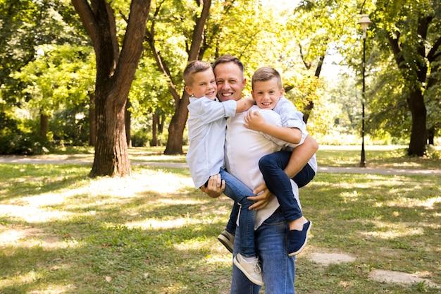 Padre posando con sus hijos. Foto gratis