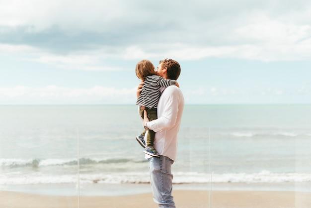 Padre que detiene al hijo pequeño en la costa Foto gratis