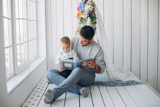 Padre sentado en casa con su pequeño hijo Foto gratis