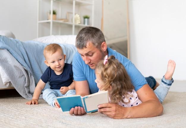 Padre sentado en el piso y leyendo para niños Foto gratis