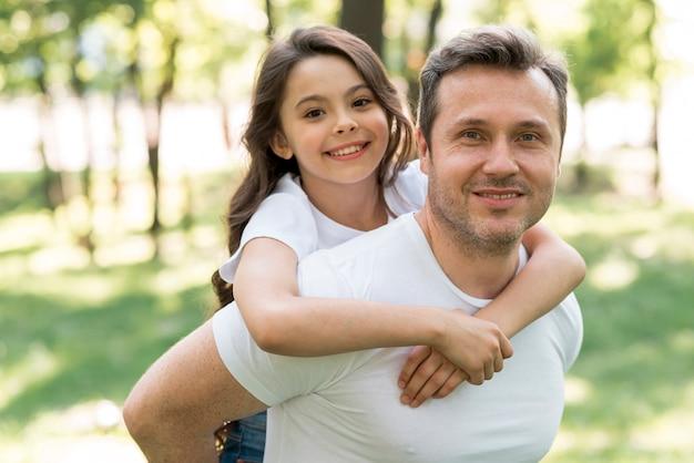 Padre sonriente que lleva a cuestas a su hija linda en el parque Foto Premium