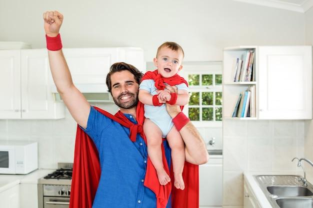Padre en traje de superhéroe hijo de elevación en la cocina Foto Premium