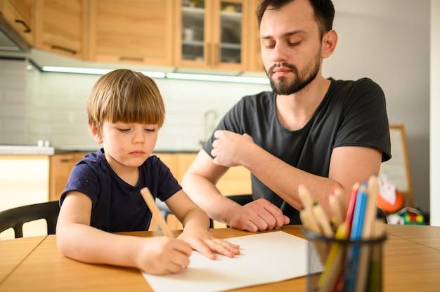 Padre viendo hijo dibujar Foto gratis