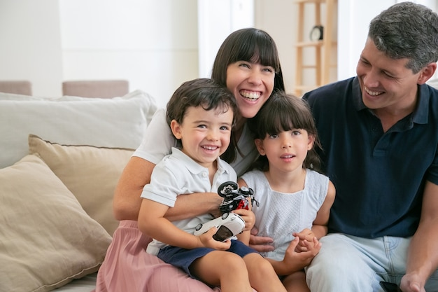 Padres divertidos alegres y dos niños viendo películas divertidas en casa, sentados en el sofá en la sala de estar y mirando a otro lado y riendo. Foto gratis