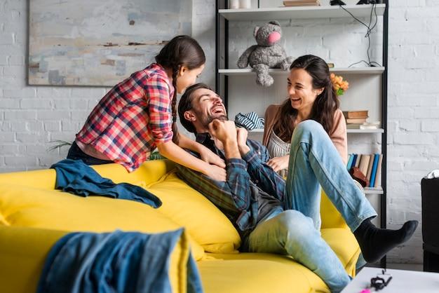 Padres e hija jugando en la sala de estar Foto gratis