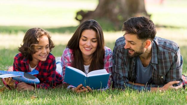 Padres e hijos leyendo mientras están juntos Foto gratis