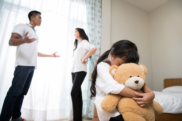 Los padres están peleando con una hija que se siente estresada. Foto Premium