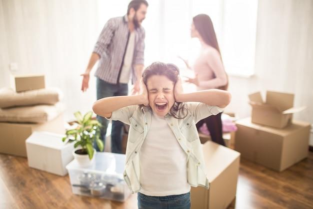 Los padres jóvenes están peleando entre sí y discutiendo. están locos el uno por el otro. su hija no está feliz por eso. ella ha cerrado sus oídos con las manos y gritando. Foto Premium
