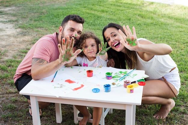 Padres con su hija mostrando sus manos desordenadas mientras pintan en el parque Foto gratis